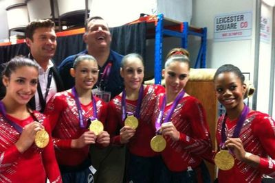<i>American Idol</i> host Ryan Seacrest bumps into the USA gymnasts after their gold medal win.