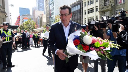 Victorian Premier Daniel Andrews lays flowers on the corner of Bourke and Elizabeth Street after a man went on a rampage in a car through busy Bourke St mall