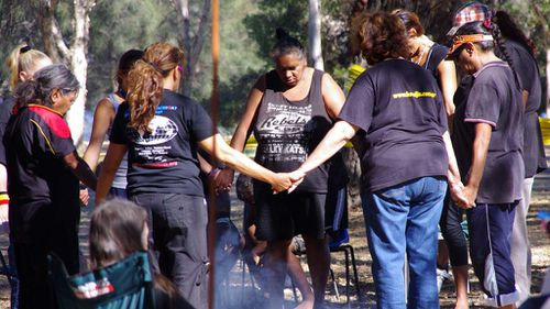 """Aboriginal women gather around a fire at a """"tent embassy"""" at Heirisson Island in Perth in 2012. (AAP)"""
