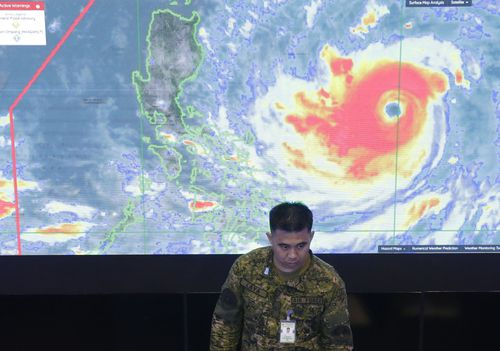 A member of the Philippine Air Force stands in front of a satellite image of Typhoon Mangkhut, locally named Typhoon Ompong, at the National Disaster Risk Reduction and Management Council operations centre in Manila.