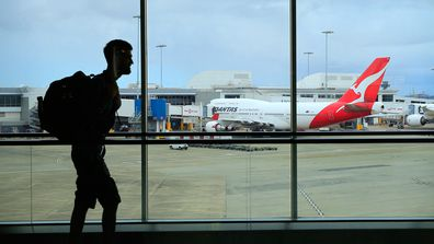 A passenger walks past a Qantas jet at the International terminal at Sydney Airport