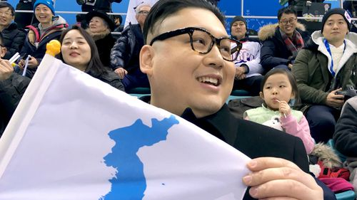 'Howard from Australia' holds a unification flag while attending the Korea-Japan women's ice hockey game. (AAP)