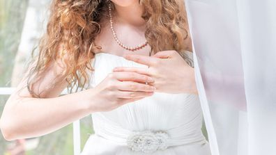 Stock image bride in wedding dress pulls off engagement ring