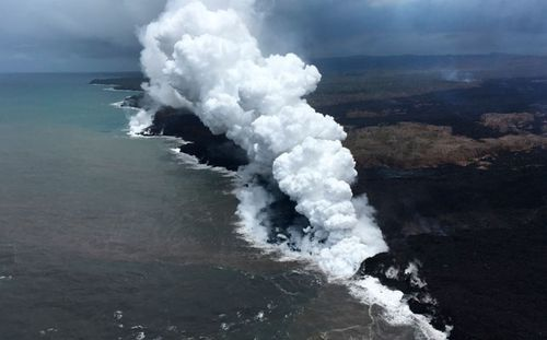 Lava sends up clouds of steam and toxic gases as it enters the Pacific Ocean as Kilauea Volcano continues its eruption cycle near Pahoa on the island of Kilauea. (AP).