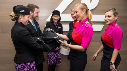 Air New Zealand staff (left) handing the jerseys over to Qantas crew. (Twitter: @FlyAirNZ)