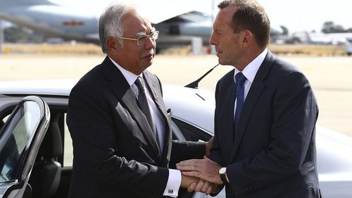 "In this April 3, 2014, file photo, Australian then Prime Minister Tony Abbott, right, shakes hands with Malaysian then Prime Minister Najib Razak as Razak prepares to depart Australia after his visit during the search of the missing Malaysia Airlines flight MH370 at Perth International Airport, Australia. Abbott has claimed the ""top levels"" of the Malaysian government long suspected the vanishing of a plane almost six years ago was a mass murder-suicide by the pilot."