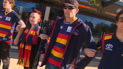 Supporters link arms in tribute to Phil Walsh. (9NEWS)