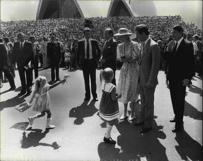 A little girl races in to present her tribute to the Princess of Wales, outside the Sydney Opera House.