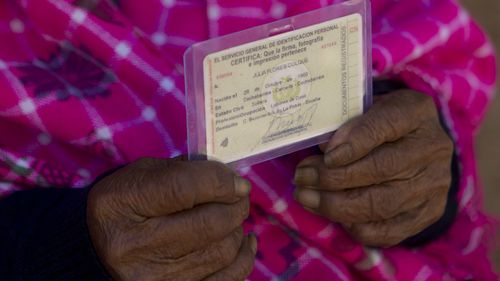 In this Aug. 23, 2018 photo, 117-year-old Julia Flores Colque holds her identification card displaying her date of birth in Sacaba, Bolivia.