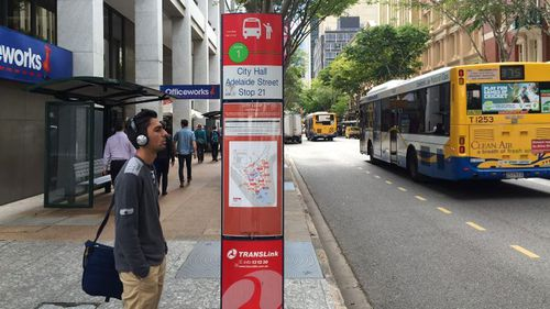A commuter in Brisbane looks at a bus timetable