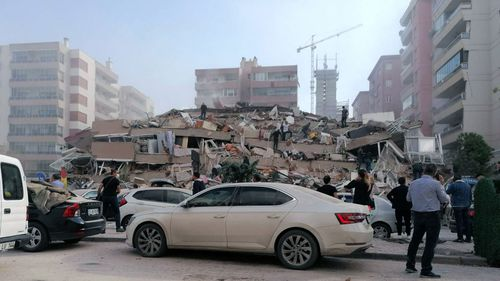 People work on a collapsed building, in Izmir, Turkey, Friday, Oct. 30, 2020, after a strong earthquake in the Aegean Sea has shaken Turkey and Greece.