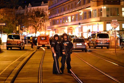 Heavily armed police stand near Schwedenplatz square in Vienna.