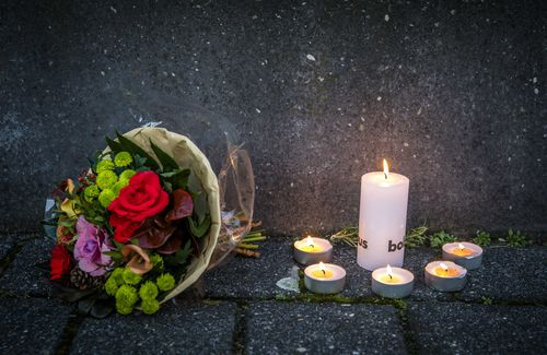 lowers and candles lie in front of the International Criminal Tribunal for the former Yugoslavia, placed after the death of Slobodan Praljak. (AAP)