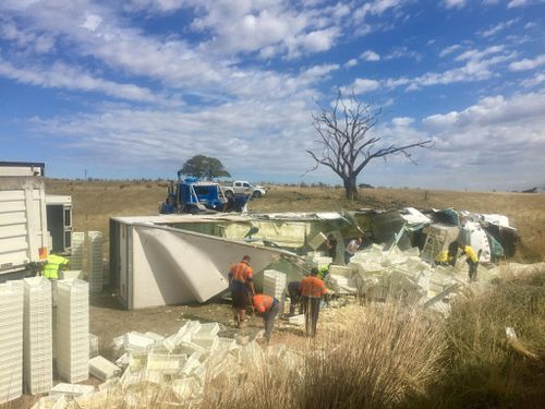 The semi-trailer rolled six metres down an embankment and landed upside down in a paddock. (Picture: Toby Vue/ Yass Tribute)