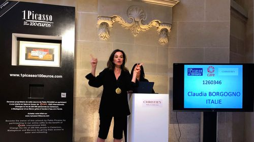 Raffle organiser Peri Cochin gestures as the name of the winner is displayed on a screen in Paris