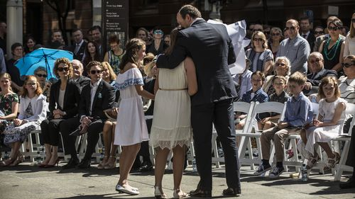 Katrina Dawsons's daughter Chloe hugs her father Paul Smith during the unveiling. (AAP)