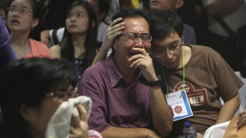Relatives of passengers aboard the AirAsia flight weep upon seeing the news on television. (AAP)