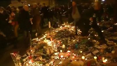 The tribute flowers and candles were trampled this morning when terrified Parisians ran for their lives. (9NEWS)