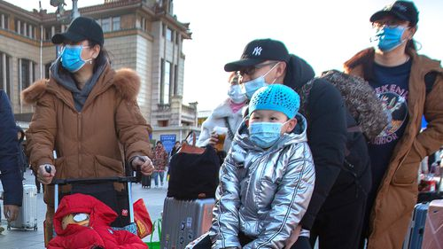 Travellers wear face masks as they walk outside of the Beijing Railway Station. China has reported a sharp rise in the number of people infected with a new coronavirus, including the first cases in the capital.