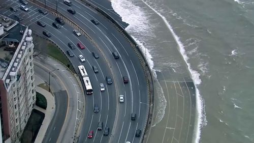 The high waves can be seen crashing onto what appears to be a motorway. (ABC-7 Chicago)