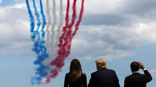 """US First Lady Melania Trump, US President Donald Trump and French President Emmanuel Macron watch as French elite acrobatic flying team """"Patrouille de France"""" (PAF) fly over after a French-US ceremony."""