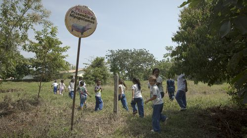 """Children walk past a sign reading in Spanish """"Danger  Presence of Hippos"""" as they arrive for class at a school near the Napoles Park in Puerto Triunfo, Colombia."""