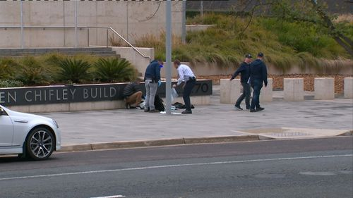 Officers and officials gather at the scene of the incident outside the ASIO building.