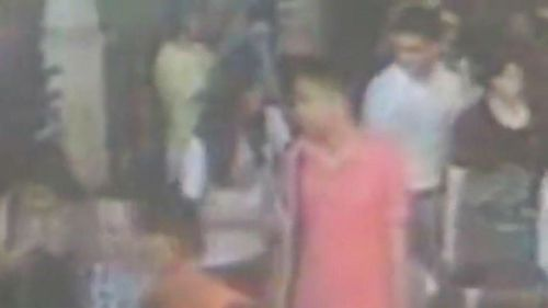 A CCTV image of two suspected accomplices in red and white shirts.