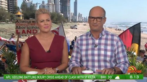 Sunrise hosts Sam Armytage and David Koch acknowledged the protesters standing behind them during the show. (Supplied)