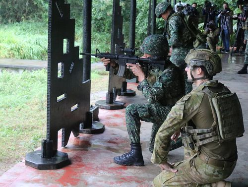 An ADF member watches a Philippine Marine firing during a training exercise at a marine base in Ternate, Cavite province, Philippines.