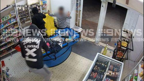 A store worker has been terrorised by machete-wielding robbers in a store.