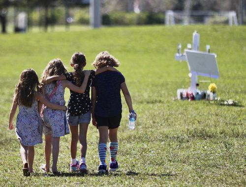 Children approach a vigil post in Parkland. (AAP)