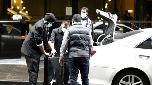Guests at the Stamford Hotel in Melbourne are seen wearing masks as they get into taxis.