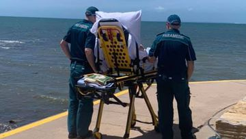 Two QAS paramedics stand alongside a patient on a stretcher near Cleveland Lighthouse in Brisbane.