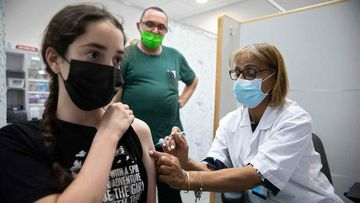 An Israeli youth receives a Pfizer-BioNTech COVID-19 vaccine in the central Israeli city of Rishon LeZion.