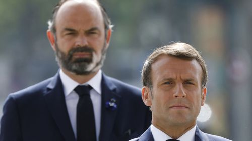 French President Emmanuel Macron, right, and French Prime Minister Edouard Philippe attend a ceremony to mark the 75th anniversary of the World War II victory over Nazi Germany, at the Arc de Triomphe in Paris, Friday May 8, 2020