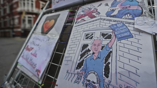 Posters featuring character of the WikiLeaks founder are fixed on a barrier in front of the Ecuadorian embassy. (AAP)