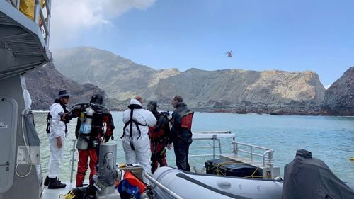 Police divers prepare to search the waters near White Island off the coast of Whakatane, New Zealand, Saturday Dec. 14, 2019. A team of nine from the Police National Dive Squad resumed their search at early Saturday for a body seen in the water following Monday's volcanic eruption