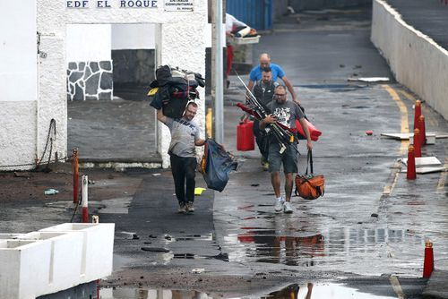 Residents take their belongings as they evacuate the apartment block in Mesa del Mar on Tenerife.
