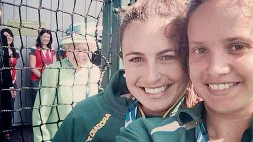 Hockeyroos Jayde Taylor and Brooke Peris, with the Queen behind them. (Twitter)
