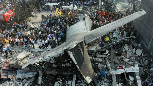 Rescuers search for victims at the site where an air force cargo plane crashed in Medan, North Sumatra. (AAP)