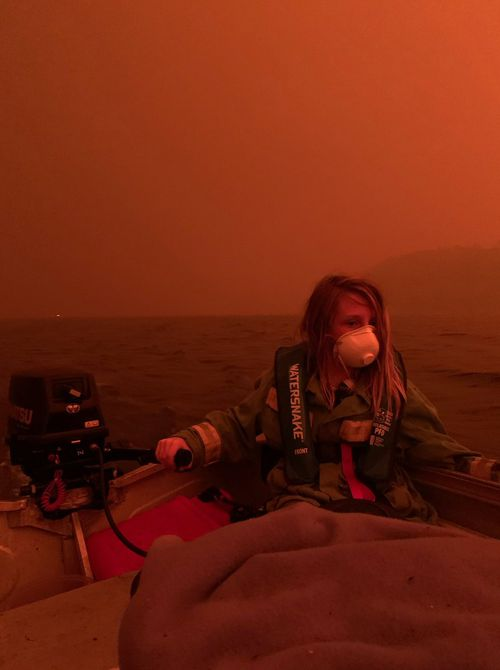 Finn Burns navigates a boat through thick smoke at Mallacoota, as fire advanced on the seaside Victorian town on December 31, 2019.