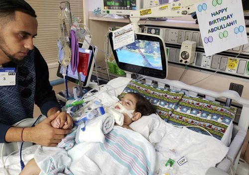 Ali Hassan with his dying 2-year-old son Abdullah in a Sacramento hospital. The boy's mother, Shaima Swileh, will catch the earliest available flight out of Egypt and is scheduled to arrive in San Francisco on Wednesday evening