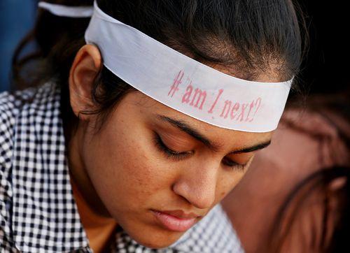 "An Indian girl wearing a ribbon saying ""#am I next"". (AAP)"