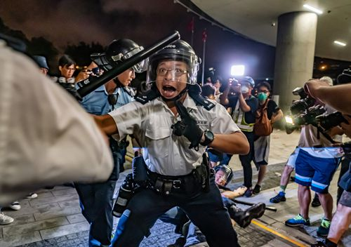 Police officers charge toward protesters after a rally against the extradition law proposal at the Central Government Complex on June 10 in Hong Kong.