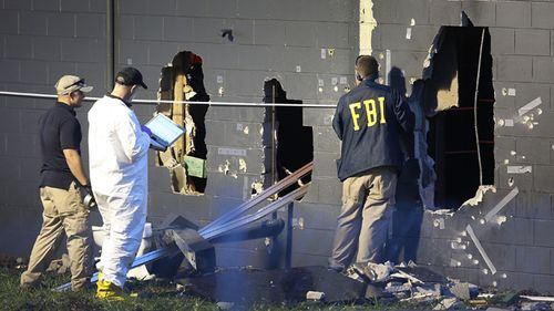 FBI agents examine the back wall of the Pulse nightclub. Source: AFP