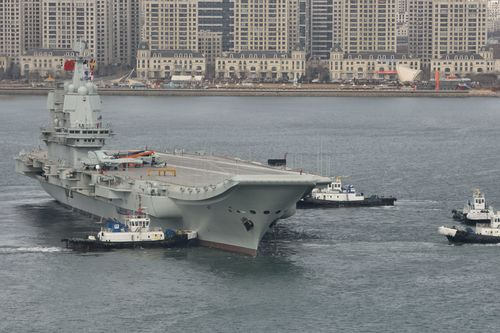 Tugboats undock China's first homemade aircraft carrier in Dalian city, north-east China.