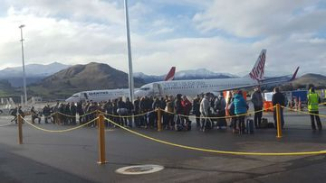 Passengers were evacuated from Queenstown Airport after a message about a bomb was found on board a plane. (Twitter/Louise Cheer)