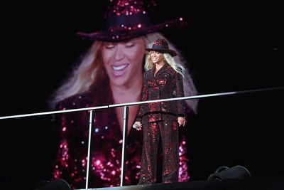 Beyoncé in a sparkling red suit, performing during her 'On The Run' tour.