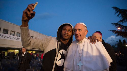 Pope Francis stopped for selfies with people at the refugee shelter outside of Rome on Holy Thursday. (AAP)